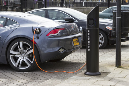 MILTON KEYNES, ENGLAND - MARCH 5, 2015: Modern electric car charging at station dock point near parking lot, United Kingdom Editorial