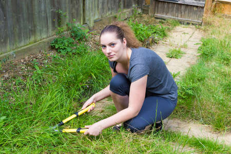 horticultural: Portrait of pretty girl cutting grass with horticultural sundry outdoors