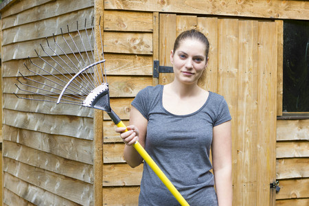 cut grass: Portrait of pretty girl raking cut grass in summer garden Stock Photo