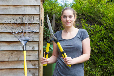 sundry: Portrait of pretty girl with horticultural sundry near backyard shed