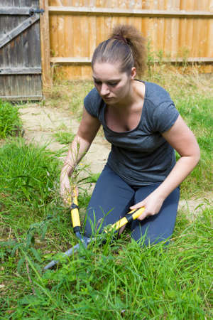 grass cutting: Portrait of pretty girl cutting grass with horticultural sundry outdoors