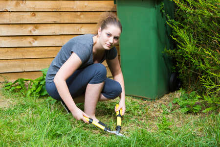 sundry: Portrait of pretty girl cutting grass with horticultural sundry outdoors