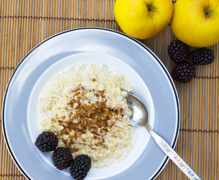 kasha: Porridge served in plate with blackberries, apples and cinnamon Stock Photo