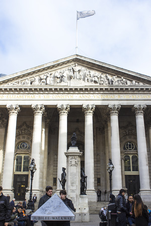 openspace: London, England - November 02, 2015: Royal Exchange building facade with columns and UK flag flapping above Editorial