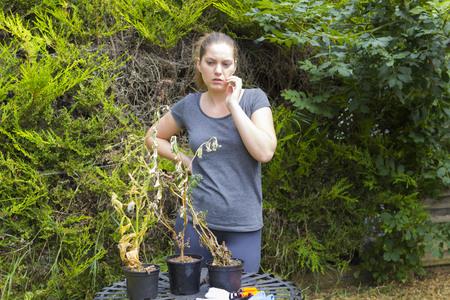 shrunken: Portrait of terrified girl with shrunken plants in backyard