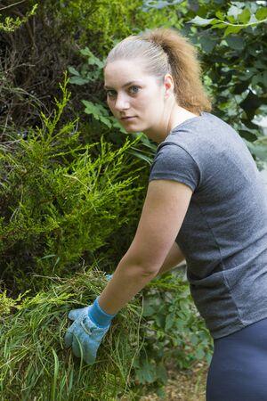 cut grass: Portrait of pretty girl collecting cut grass in summer garden