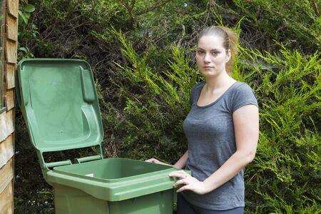 garden waste: Portrait of young woman near conteiner for garden waste Stock Photo