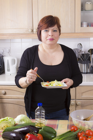 alone person: Postrit of mature woman eating tasty salad in kitchen Stock Photo