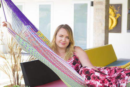 lounging: Blonde girl with long hair lounging in hammock outdoors