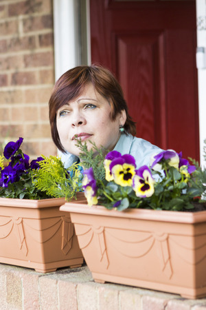 decorative balconies: Portrait of cheerful mature woman with decorative flowers in pots
