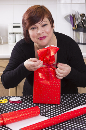 45 50 years: Portrait of happy middle aged woman wrapping presents