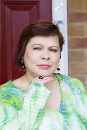householder: Portrait of mature woman at house entrance Stock Photo