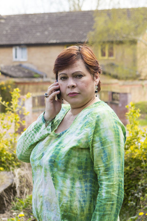 unpleasant: Worried woman receiving unpleasant call on mobile outdoors