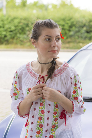 Young woman in Romanian style blouse near car