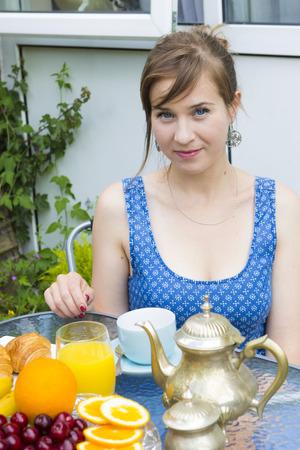 breakfast garden: Breakfast in summer garden - young woman drinking coffee Stock Photo