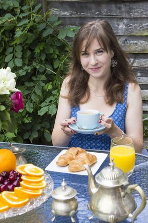 breakfast garden: Charming girl having breakfast in summer garden