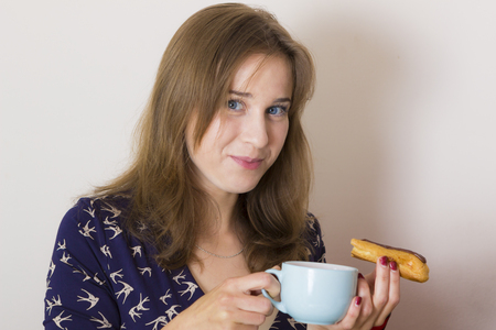 sweettooth: Portrait of sweet tooth girl enjoying eclairs and coffee