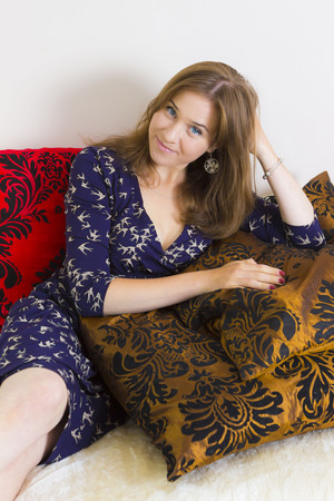 sitter: Relaxed long-haired female resting on cushions at home