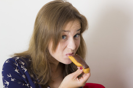 sweet tooth: Portrait of sweet tooth girl enjoying eclairs and coffee