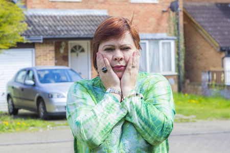 householder: Unhappy woman in front of house and parked car outdoors