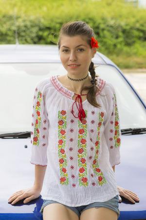 blusa: Joven en la blusa estilo rumano cerca del coche Foto de archivo
