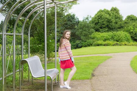Long-haired teenage girl in summer park Stock Photo