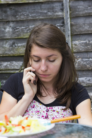 Upset young woman receiving bad news on phone