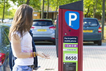 milton: MILTON KEYNES, ENGLAND - JULY 27, 2016: Female customer paying for parking the car using installed machine outdoors, UK