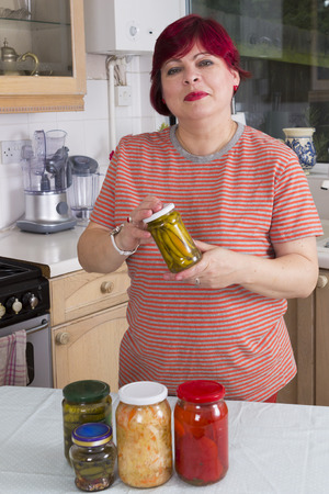 Happy mature housewife posing with homemade pickles in kitchen
