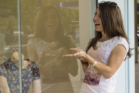 displays: Excited female customer watching shop window displays outdoors