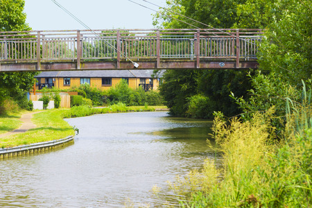 quite: MILTON KEYNES, ENGLAND - JULY 20, 2016: Summer view at New Bradwell residential area with pedestrian bridge over Grand Union Canal Editorial