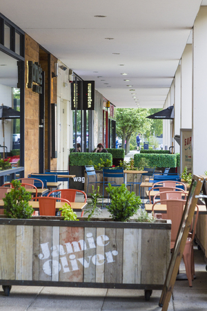 milton: MILTON KEYNES, ENGLAND - JULY 27, 2016: Summer terrace of Jamies (Jamie Oliver)  Italian restaurant in MK centre with avaliable tables