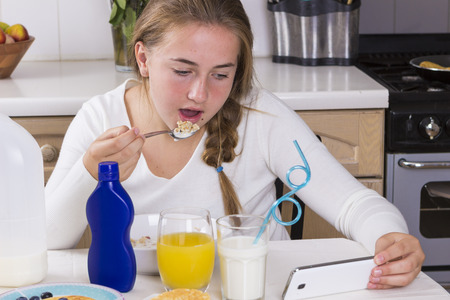 comiendo cereal: Teenage girl eating cereal and reading texts in kitchen