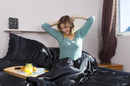Young woman waking up in home bed