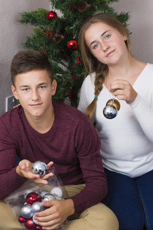 decorating christmas tree: Teen couple decorating Christmas tree at home Stock Photo