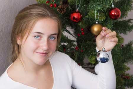 decorating christmas tree: Portrait of girl decorating Christmas tree at home