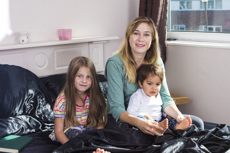 wellness sleepy: Happy mother with children posing in bed