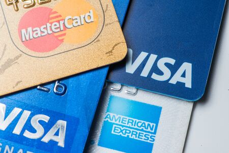Close up of credit cards with MasterCard,Visa and American Express logos on white background,illustrative editorial Editorial