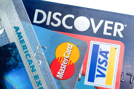 Close up of credit cards with Discover,American Express,visa and MasterCard logos on white background,illustrative editoria Editorial