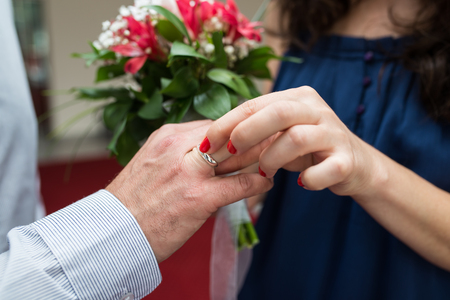 A closeup of a bride putting a wedding band on the groom's finger