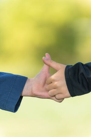 Two kids hands having a thumb war on a blurred background