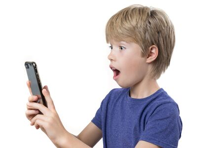 Portrait of a surprise young boy looking at smartphone, on white background Banco de Imagens