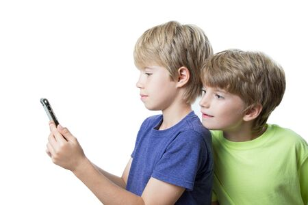 Portrait of a two boys looking at a smartphone, on white background Banco de Imagens