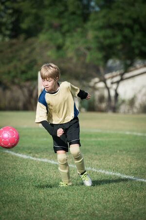 Portrait of a boy playing soccer, ready to kick the ball