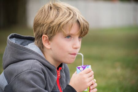 Portrait of a kid drinking juice with a straw