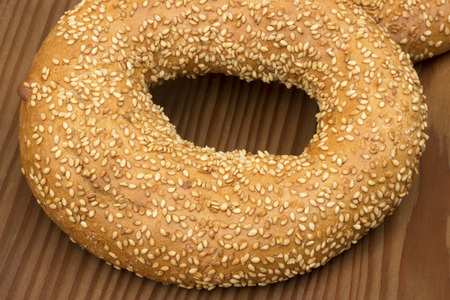 sesame seeds: Bagel with sesame seeds on old wooden background. Stock Photo