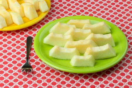 checkered tablecloth: Freshly cut melon on checkered tablecloth. Stock Photo