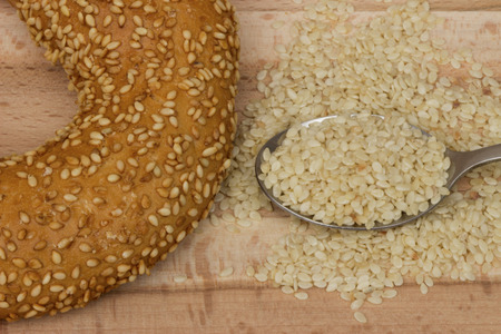 A close up of a sesame seed bagel, viewed from above on wooden background. photo