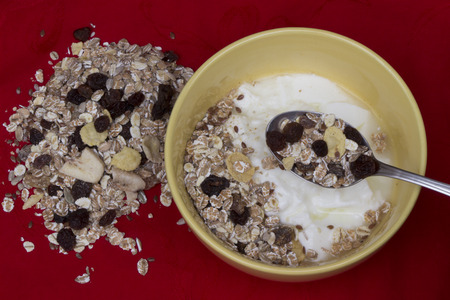 red tablecloth: Yogurt with muesli on red tablecloth. Stock Photo