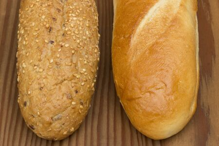 Two types of baguettes on wooden background. photo